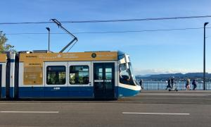 A blue and white tram is crossing a bridge in Zurich.