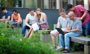 The photo shows seven students sitting and learning in small groups on benches outside.