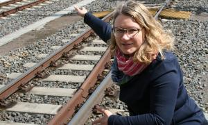 A woman with blond hair and glasses squats by a railway track and points at something.