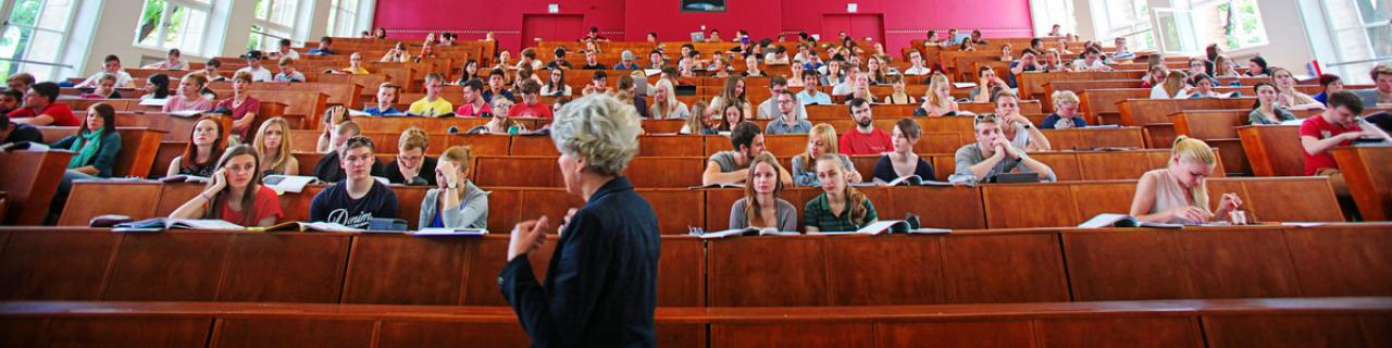 The photo shows a lecture hall full of students. In the foreground you can see the lecturer.