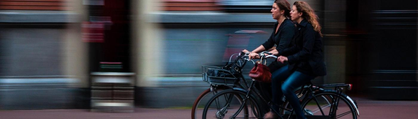 Two women cycling next to each other.